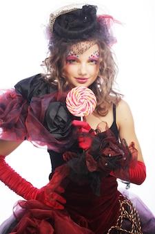Meisje met met creatieve make-up houdt lolly.