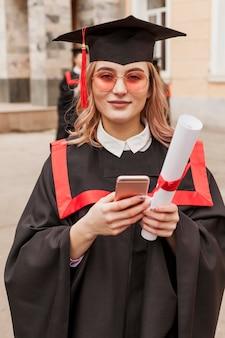 Meisje met mobiel bij afstuderen