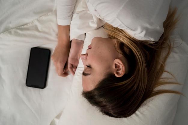 Meisje met mobiel tijdens het slapen