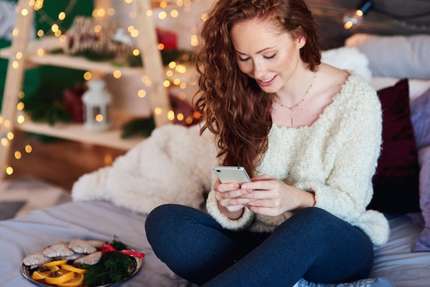 Meisje met mobiele telefoon kersttijd doorbrengen in bed