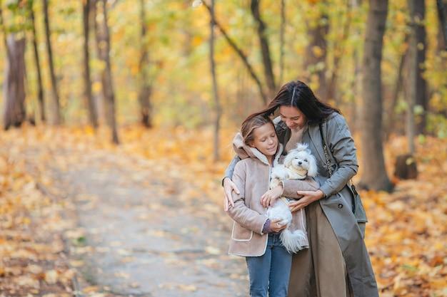 Meisje met moeder buiten in park op herfstdag