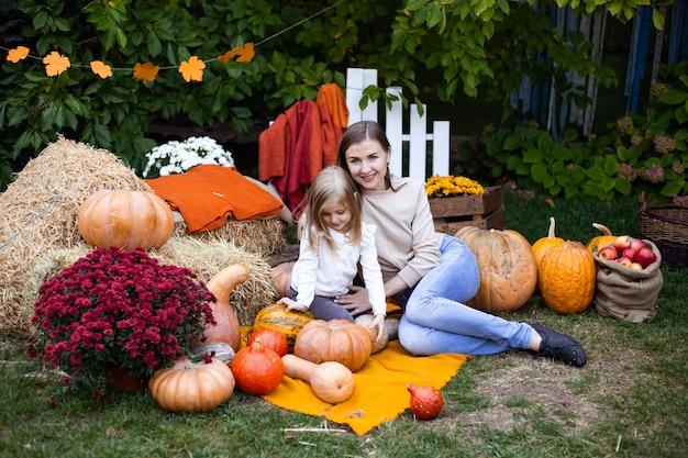 Meisje met moeder buitenshuis met pompoenen