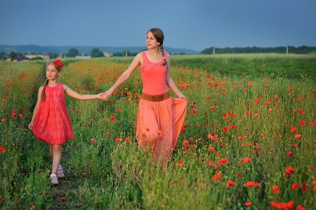 Meisje met moeder die op een papavergebied loopt