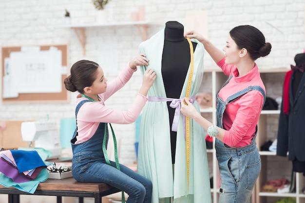 Meisje met moeder in de naai-atelier.
