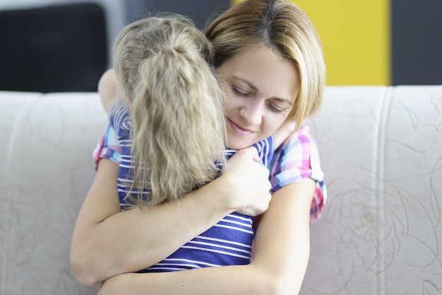 Meisje met moeder knuffelen op de bank thuis