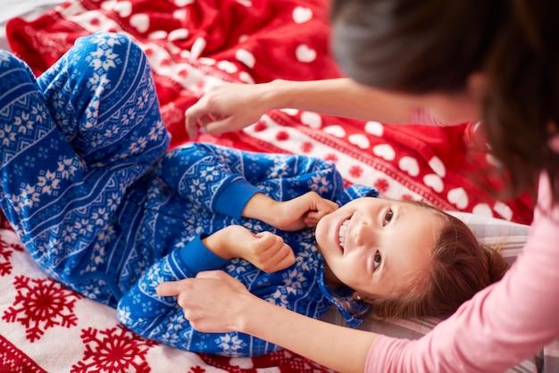 Meisje met moeder samenspelen in het bed