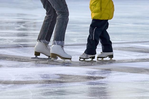 Meisje met moeder schaatsen op de ijsbaan. sporten en amusement. rust- en wintervakanties.