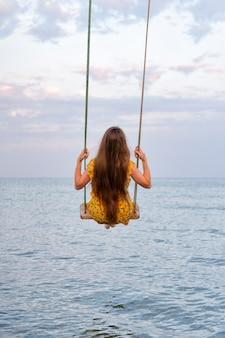 Meisje met mooi lang haar zit op schommel boven zee