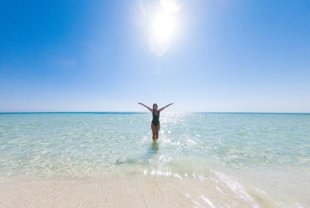 Meisje met mooi sportfiguur geniet van het warme blauwe water van de rode zee op het zand