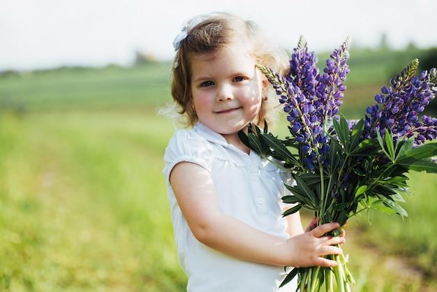 Meisje met mooie blauwe bloemen op een zonnige zomeravond.