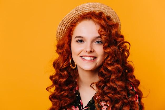 Meisje met mooie blauwe ogen en weelderige wimpers glimlacht oprecht. close-upportret van gemberdame in schipper op geïsoleerde ruimte.