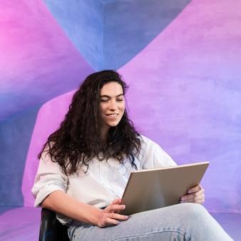 Meisje met mooie haren die op laptop werkt