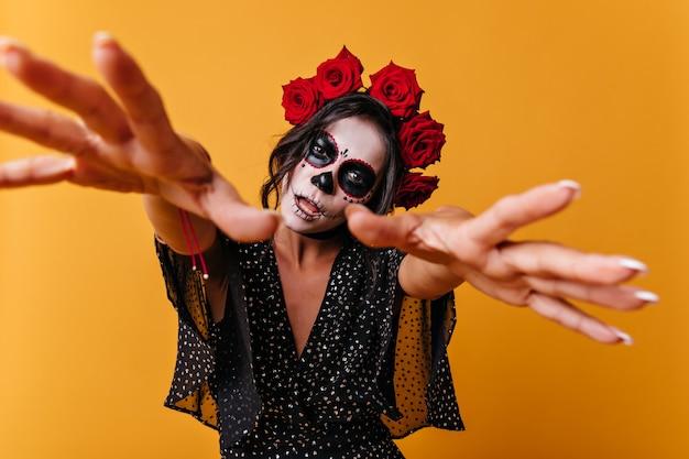 Meisje met mooie maar beangstigende gezichtskunst trekt als een zombie handen naar de camera. portret van ongebruikelijke vrouw met rode rozen in haar haar.