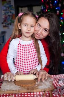 Meisje met mooie moeder de peperkoekkoekjes van kerstmis van het moederbaksel samen