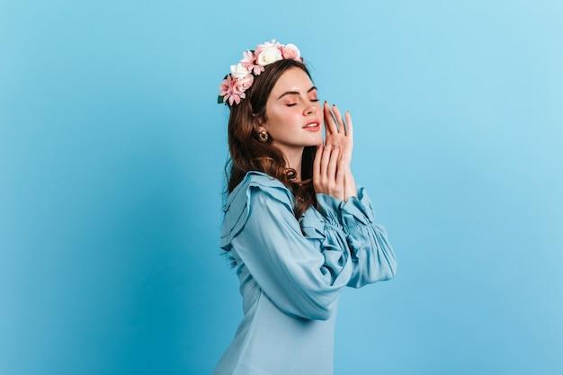 Meisje met naakte make-up raakt zachtjes haar gezicht. schot van krullende brunette in hemelsblauwe jurk op geïsoleerde muur.