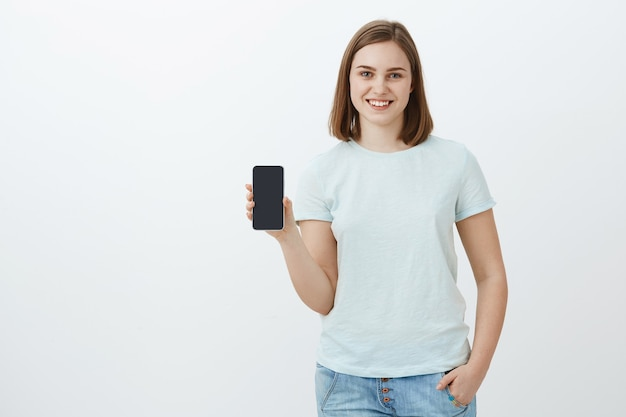 Meisje met nieuwe telefoon die ouders hebben gekocht voor een nieuwe schoolperiode. opgetogen en tevreden charmante jonge vrouw die het smartphonescherm toont en praat over een coole app die ze in de online winkel over een grijze muur heeft gevonden