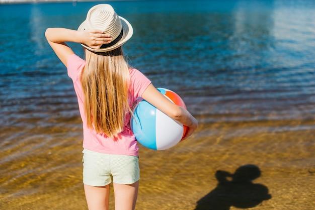 Meisje met opgeblazen bal die water bekijkt