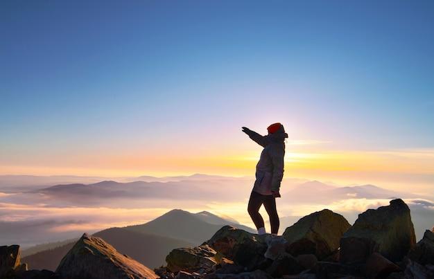 Meisje met opgeheven hand op de bergtop bij mooie ochtendzonsopgang.