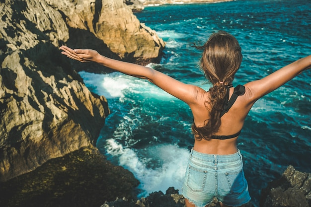 Meisje met opgeheven handen geniet van uitzicht op de oceaan