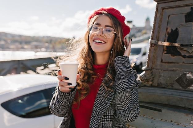 Meisje met opgewonden gezichtsuitdrukking koffie drinken op straat in winderige koude dag vangen