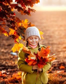 Meisje met oranje herfst esdoorn bladeren in haar handen