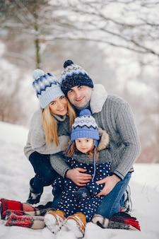 Meisje met ouders die op een deken in een de winterpark zitten
