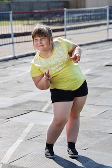 Meisje met overgewicht in sportkleding met glimlach poseren