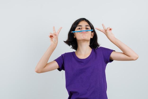 Meisje met overwinning gebaar, plezier met potlood in t-shirt