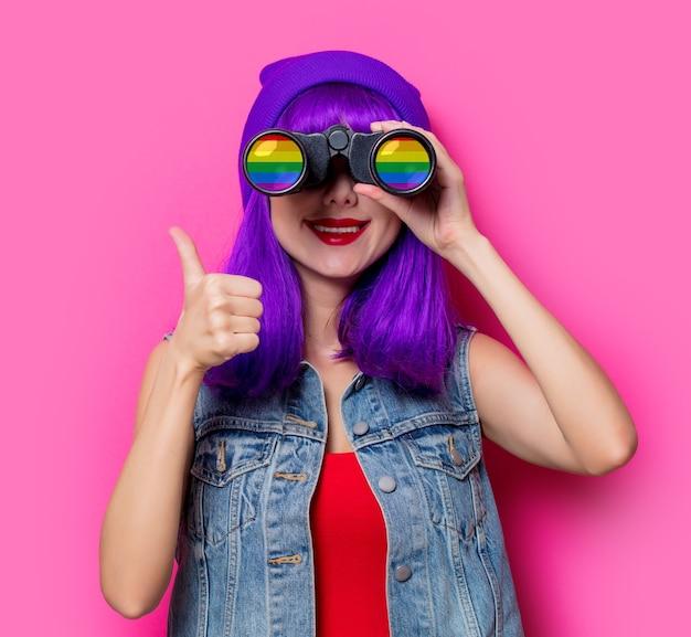 Meisje met paars haar en een regenboogverrekijker op roze