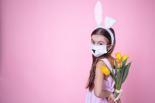 Meisje met paashaasoren en het dragen van een medisch gezichtsmasker houdt een boeket tulpen in haar handen op een roze