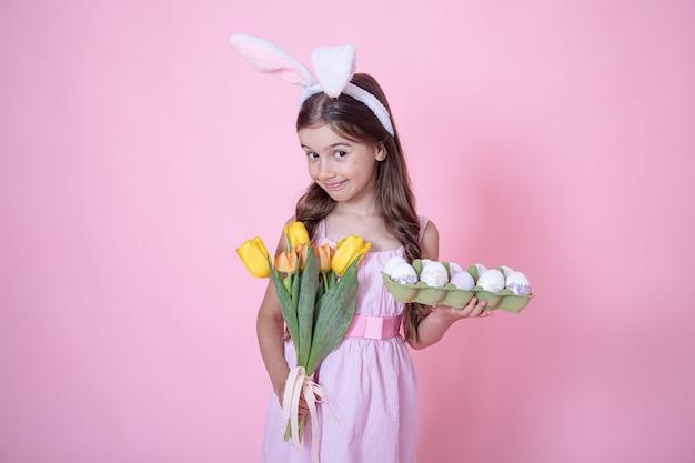 Meisje met paashaasoren houdt een boeket tulpen en een dienblad met eieren in haar handen op roze