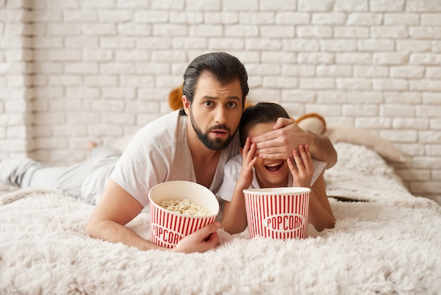 Meisje met papa bekijk enge film en eet popcorn.