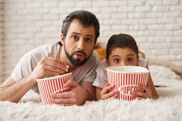 Meisje met papa kijk enge film en eet popcorn.