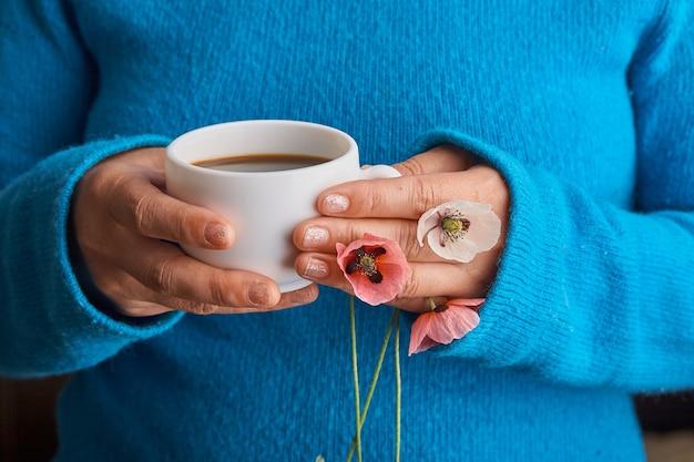 Meisje met papaverbloemen en een witte kop warme koffie in de ochtend. blauwe achtergrond.