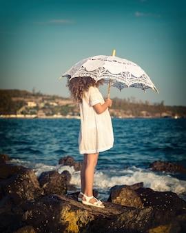 Meisje met paraplu in de buurt van de zee