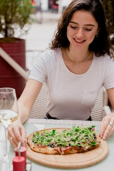 Meisje met pinsa romana in café op zomerterras. jonge vrouw die pinsa eet en wijn drinkt.