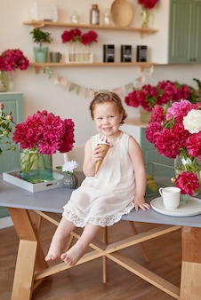 Meisje met pioenrozen boeket en met ijs. boeket pioenrozen. kindmeisje met bloemen. dag van de bescherming van kinderen. emoties van geluk en vreugde. moederdag. gelukkige jeugd