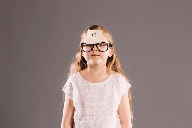Meisje met plakbriefje op voorhoofd