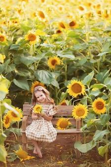 Meisje met plezier onder bloeiende zonnebloemen onder de zonsondergangstralen van de zon. meisje zittend op een bankje