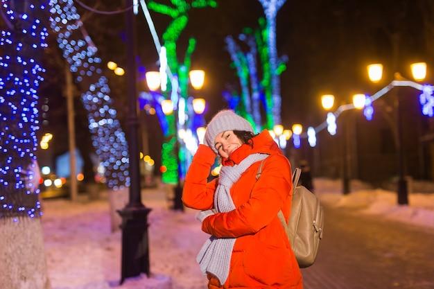 Meisje met plezier op kerstversiering lichten straat jonge, gelukkig lachende vrouw die stijlvol draagt