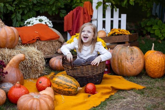 Meisje met pompoenen openlucht, de herfstachtergrond