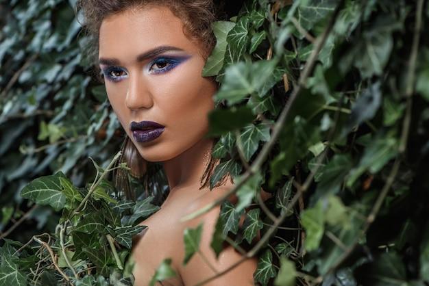 Meisje met professionele make-up, verleidelijk kijkend naar zijverpakking in groene klimop.