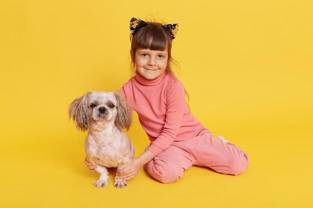 Meisje met puppy die binnen stellen en op geel glimlachen