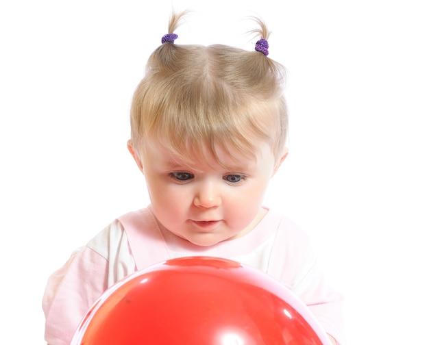 Meisje met rode ballon in handen en lachend, verbaasde uitdrukking op gezicht. foto van baby geïsoleerd op een witte achtergrond