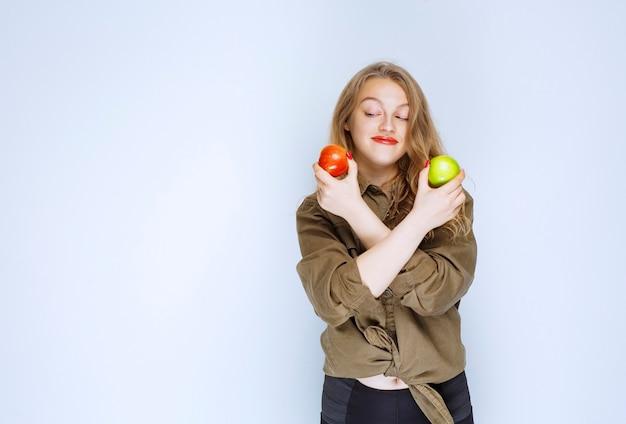 Meisje met rode en groene appels in beide handen.