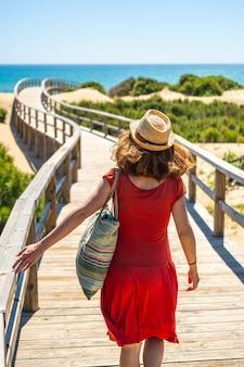 Meisje met rode jurk op het houten pad naar playa moncayo in guardamar del segura naast torrevieja, alicante