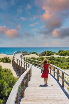 Meisje met rode jurk op het houten pad naar playa moncayo in guardamar del segura naast torrevieja