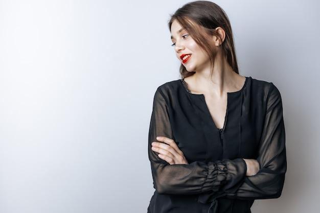 Meisje met rode lippen en een zwarte blouse kruist haar handen
