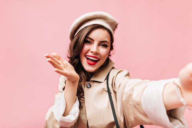 Meisje met rode lippen gekleed in beige trenchcoat en hoed waait kus en neemt selfie op roze achtergrond.