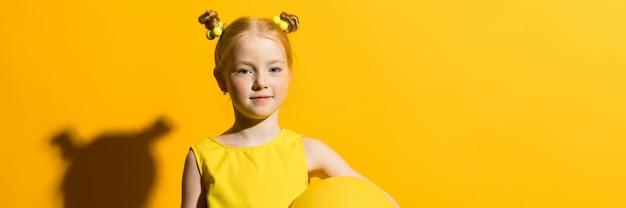 Meisje met rood haar op een gele achtergrond. het meisje houdt een gele luchtballon vast.